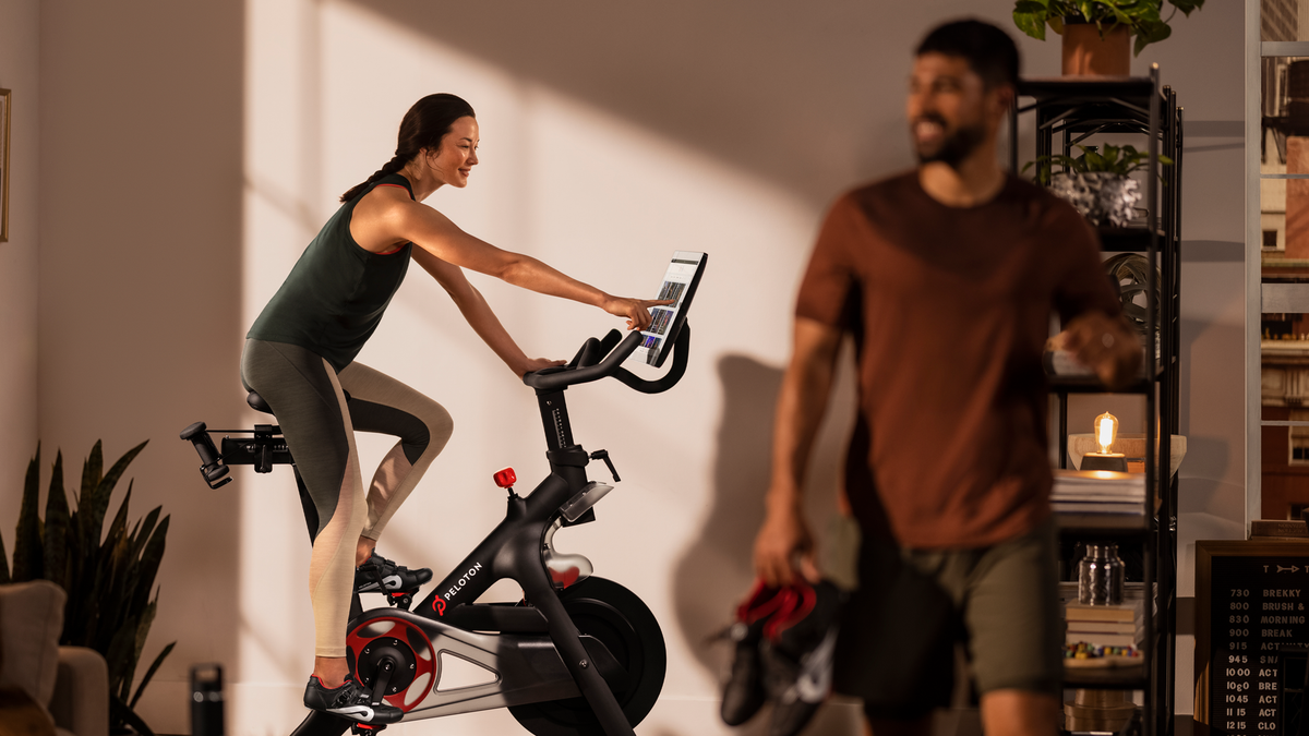 A woman rides a Peloton bike in her living room.