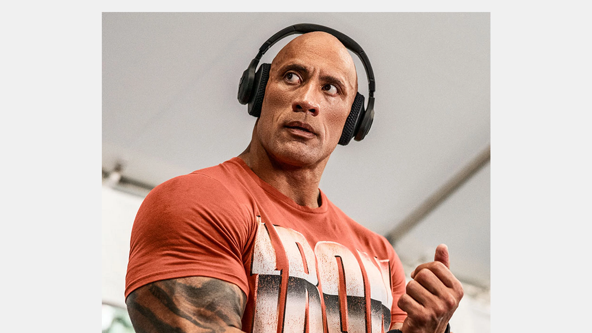 The Rock wearing his pair of UA Project Rock Over-Ear Training Headphones.f