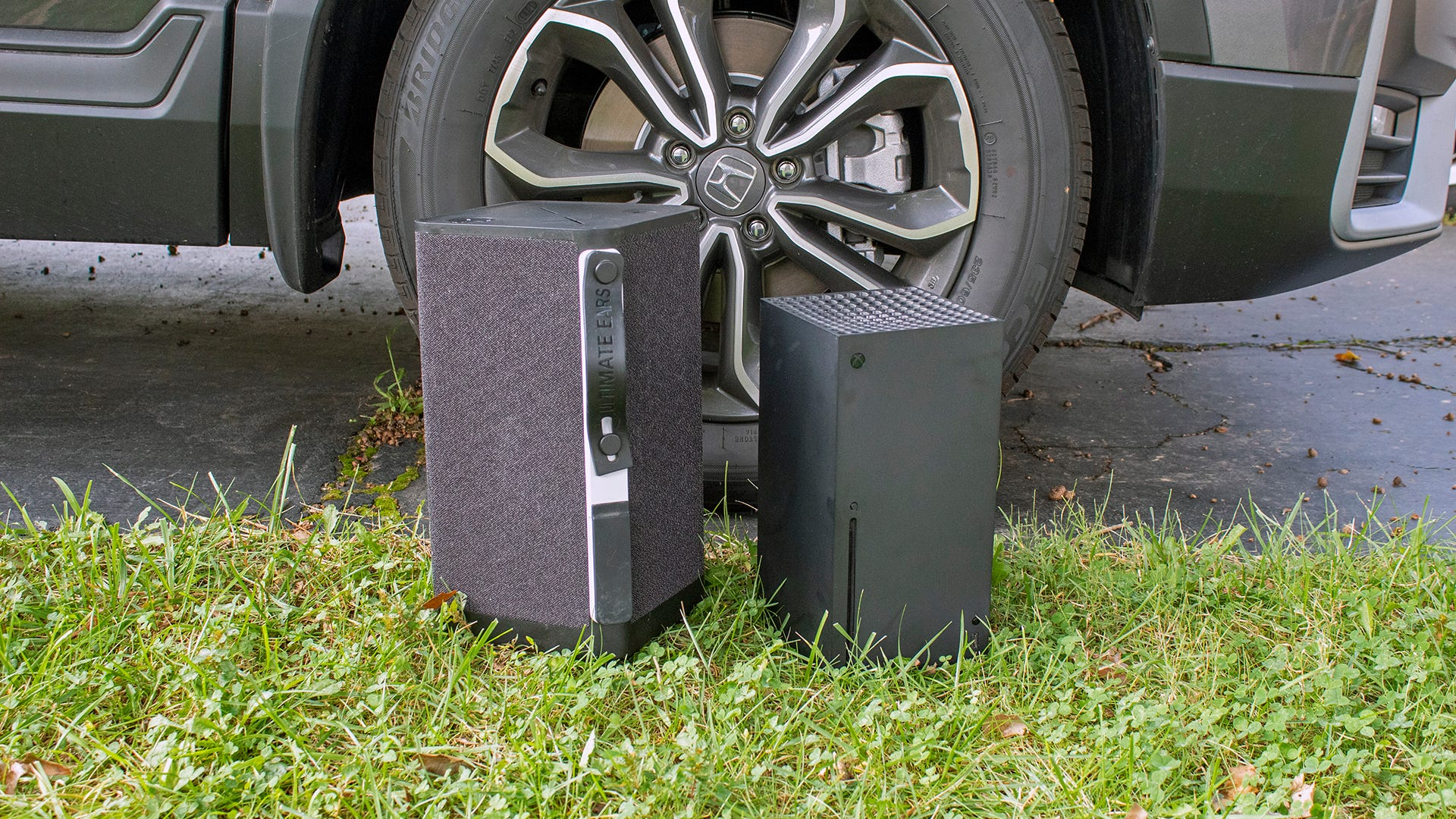 A large portable speaker next to a smaller Xbox Series X