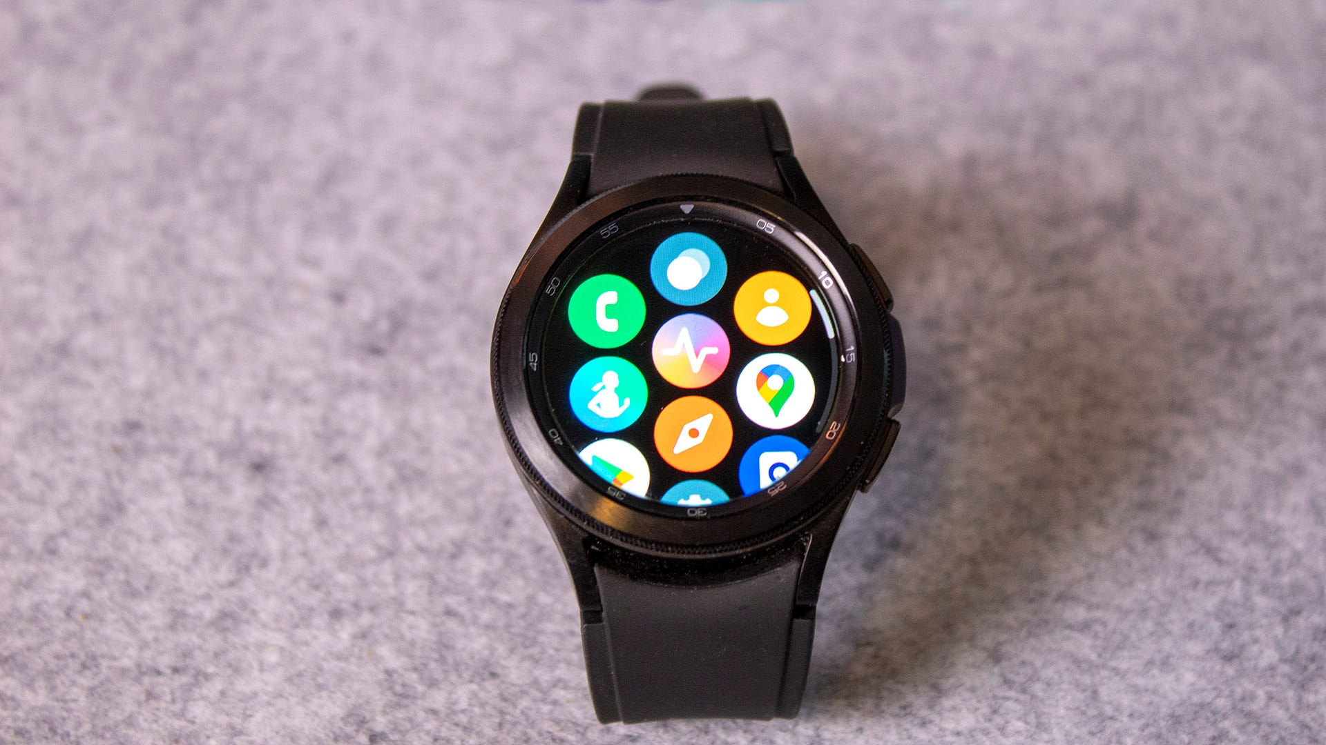 A Galaxy Watch 4 with Wear OS apps on the screen