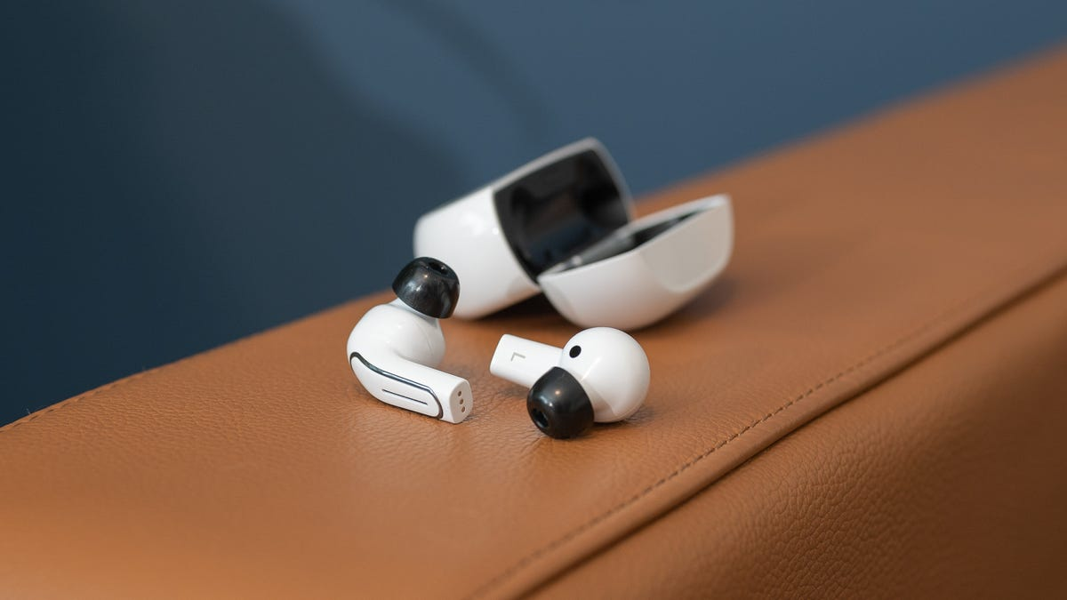 A set of white earbuds next to a case