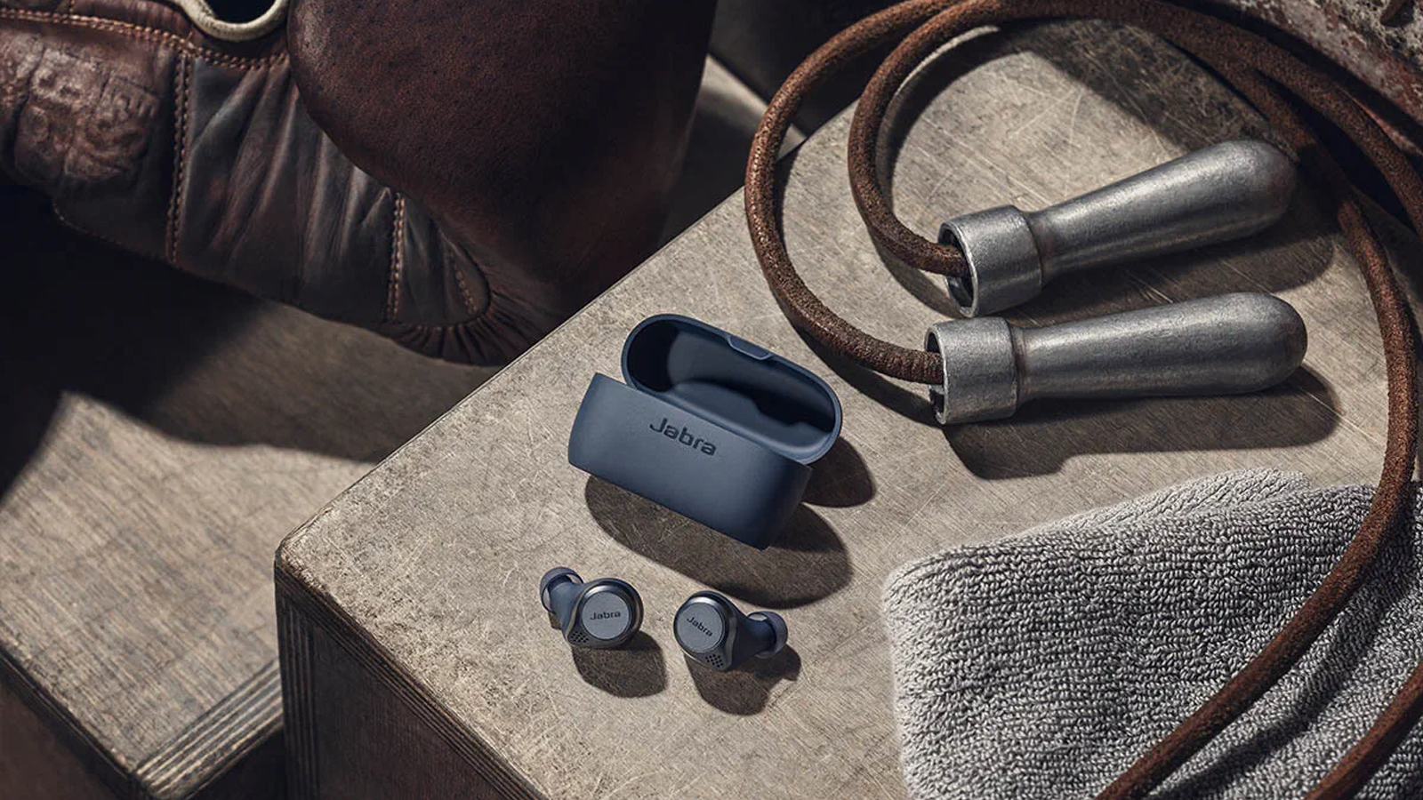 Jabra Elite Active 75t earbuds next to open case in boxing gym setting