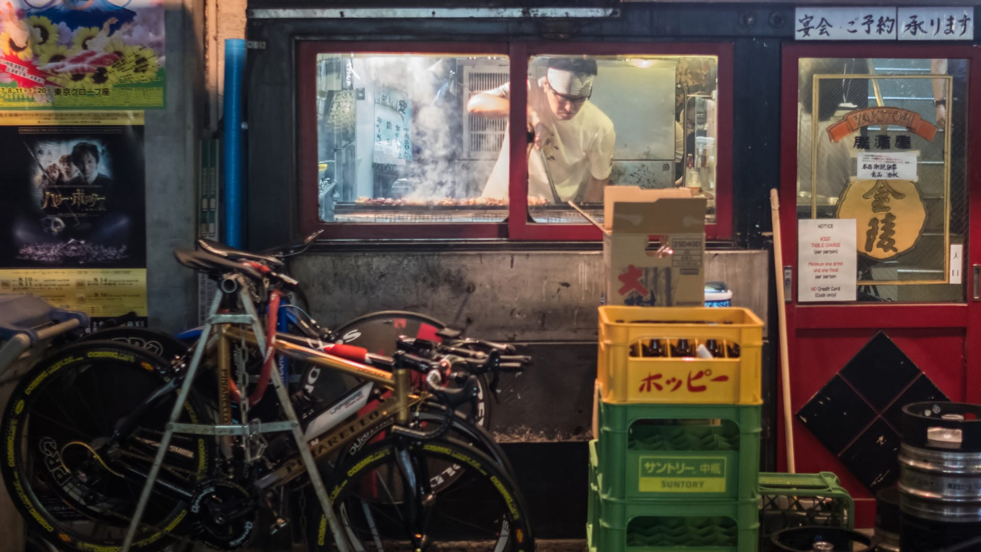 Chef cooking in small eateries, in Yurakucho Alley near a Japanese railway.