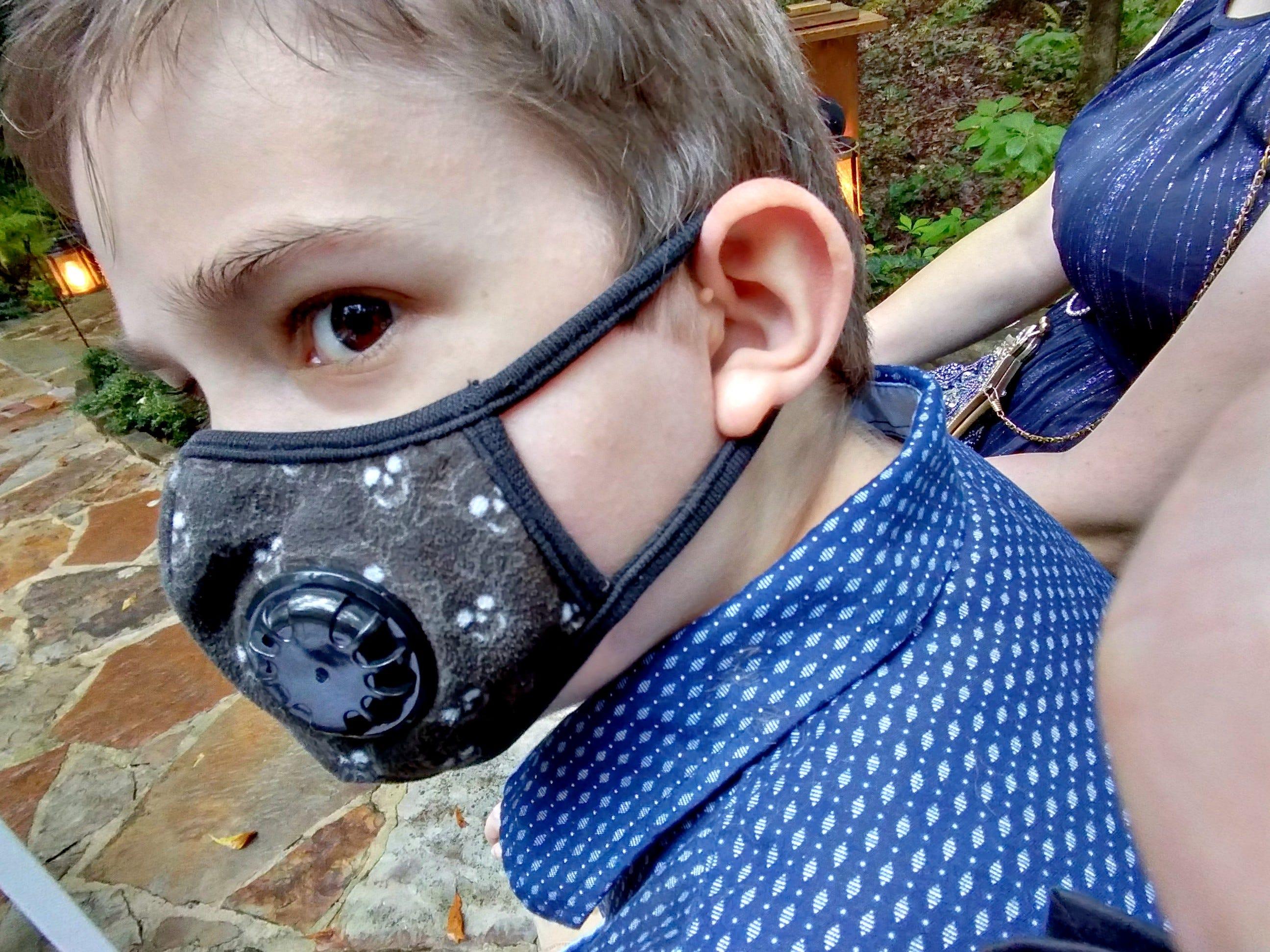A closeup of a cute little kid wearing a mask