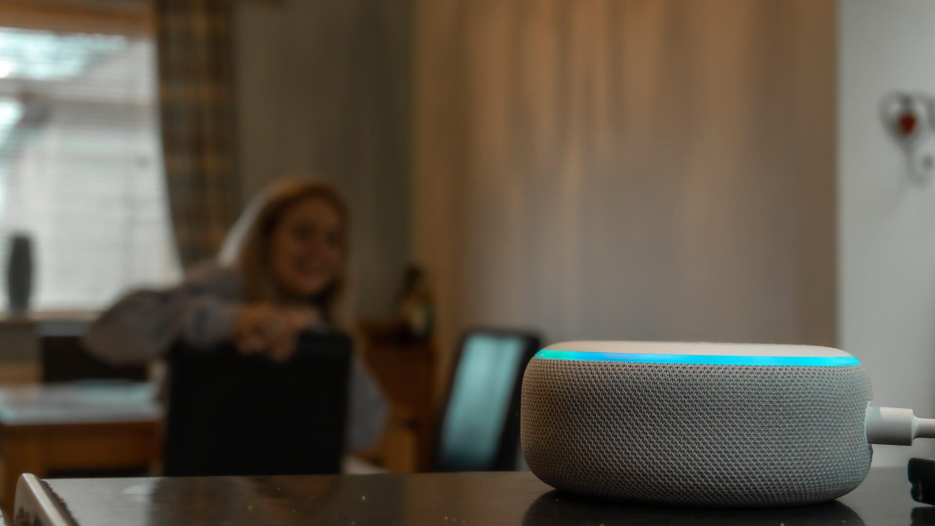 Kaşlarını çatarken bir Amazon Echo noktasıyla konuşan bir kadın.