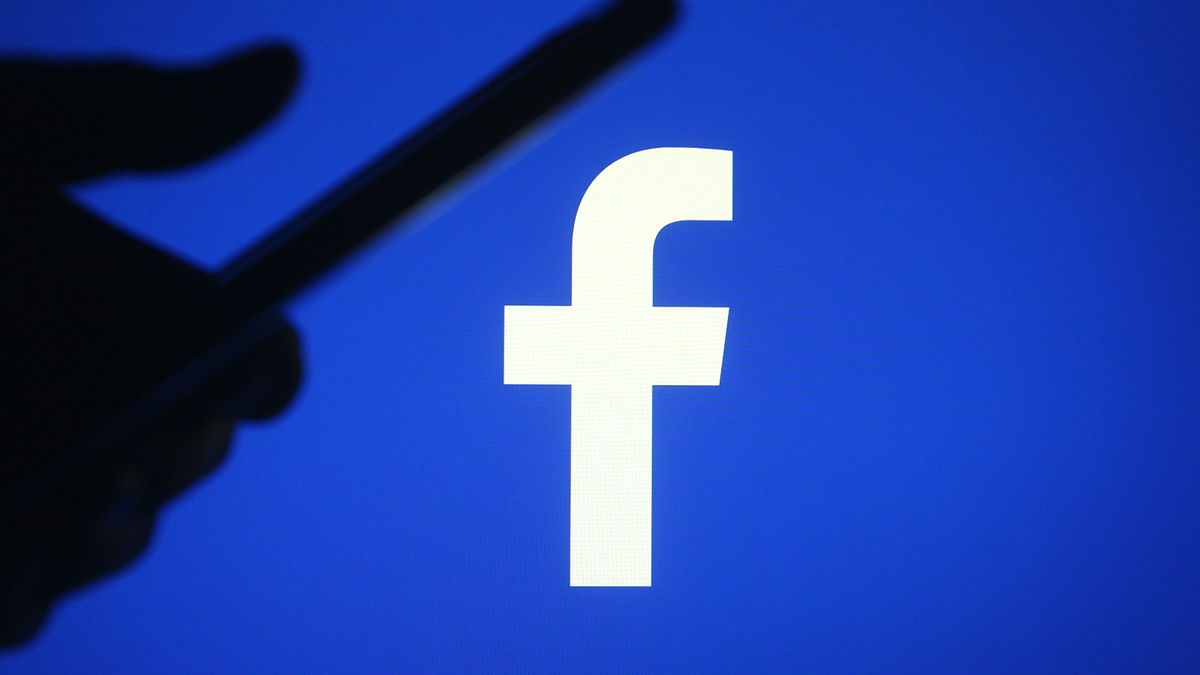 The Facebook logo with a silo cap of one hand using a smartphone.