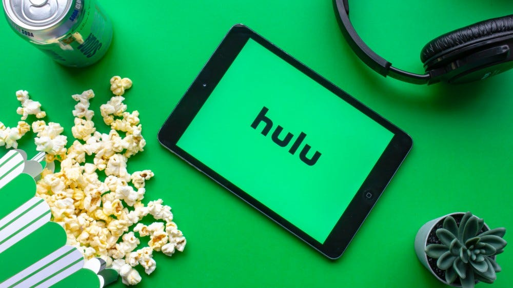 An iPad with the Hulu logo on the screen on a green background with popcorn and headphones