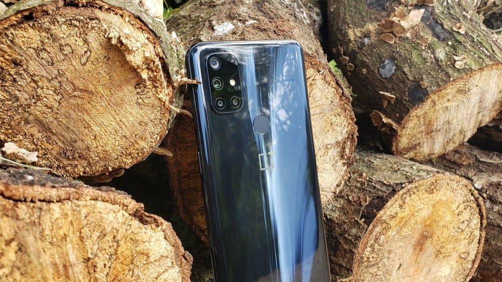 A photo of the OnePlus Nord N10 5G and some firewood.