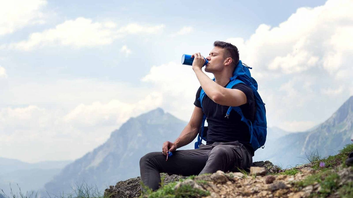 Man drinking water from an insulated water bottle while hiking on a mountain top