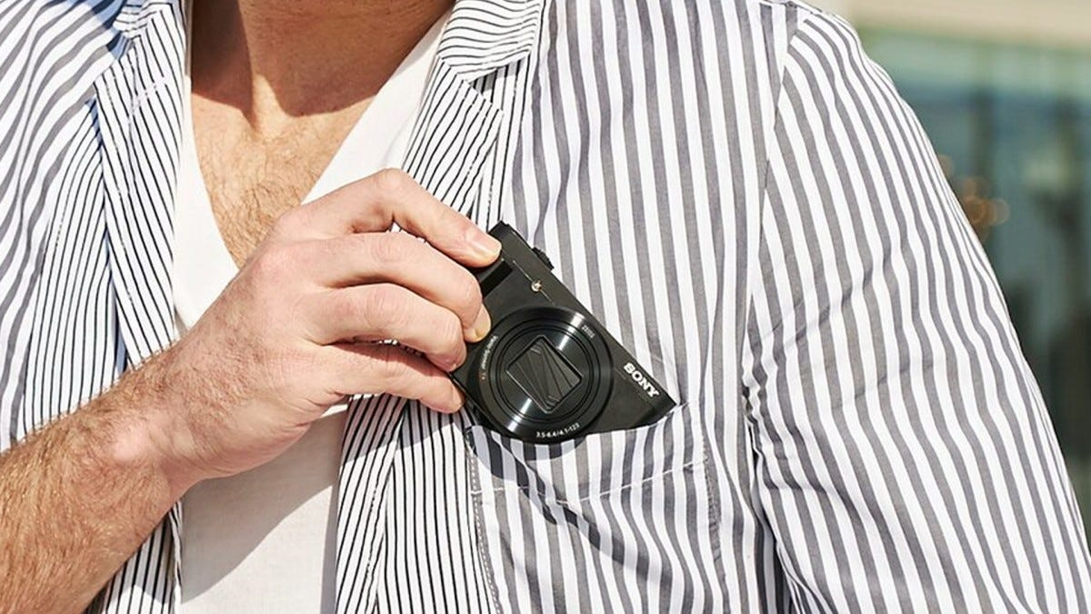 A man sticking a Sony compact camera into his pocket.