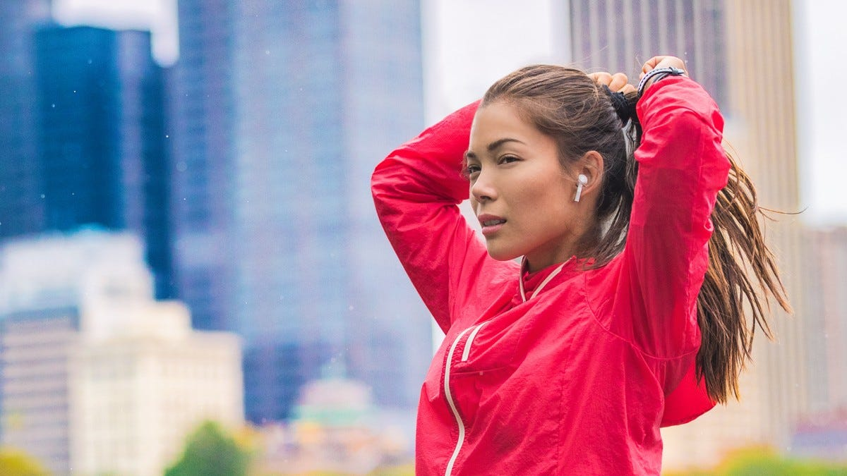 A jogger wears AirPods while running through the city.