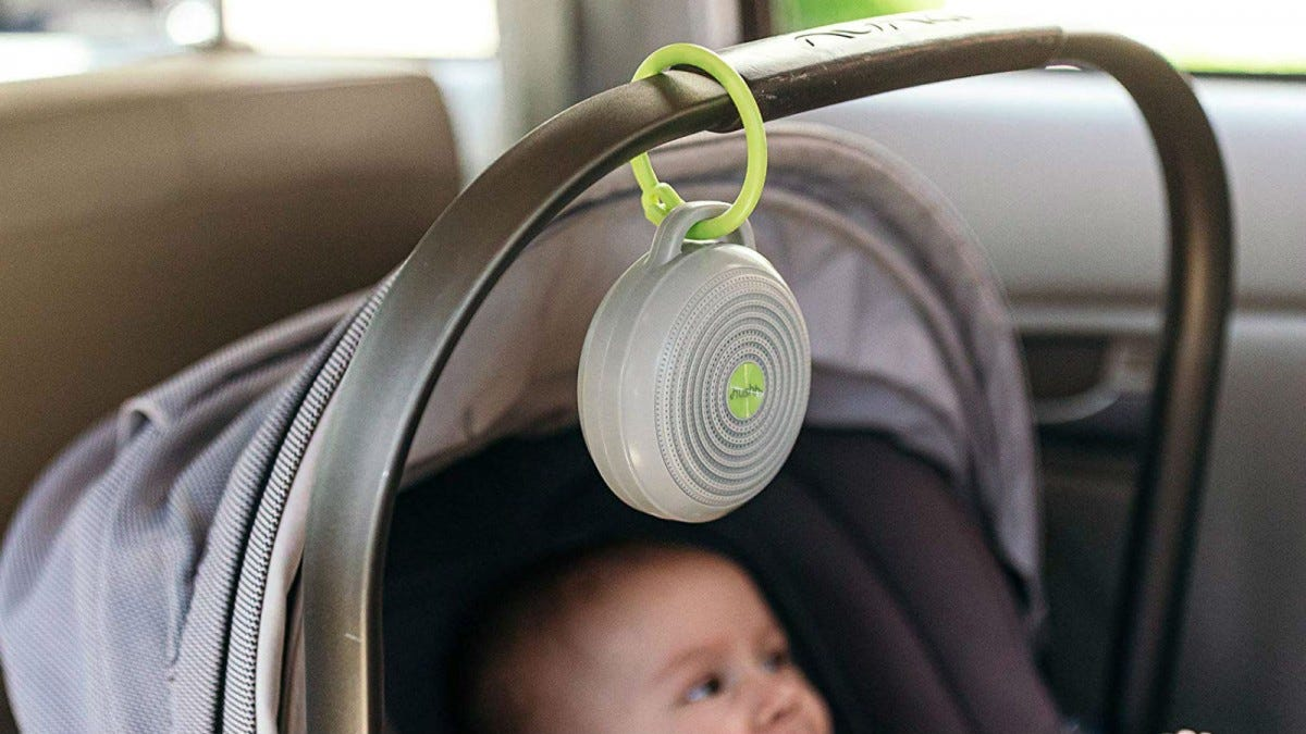 The Marpac Hushh Portable White Noise Machine hanging from a stroller handle over a baby sitting inside.