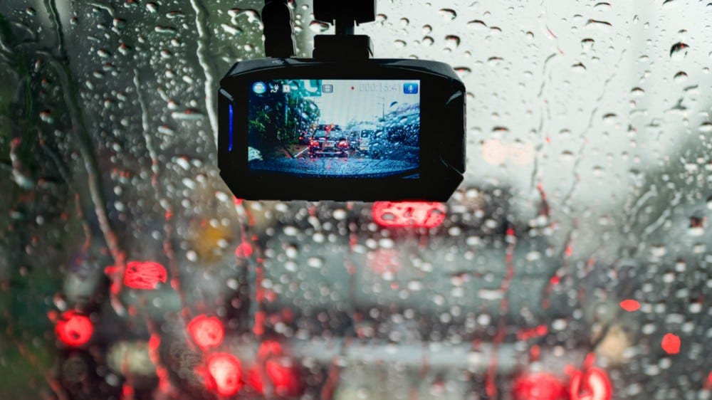Car dash cam running mounted to a rainy windshield