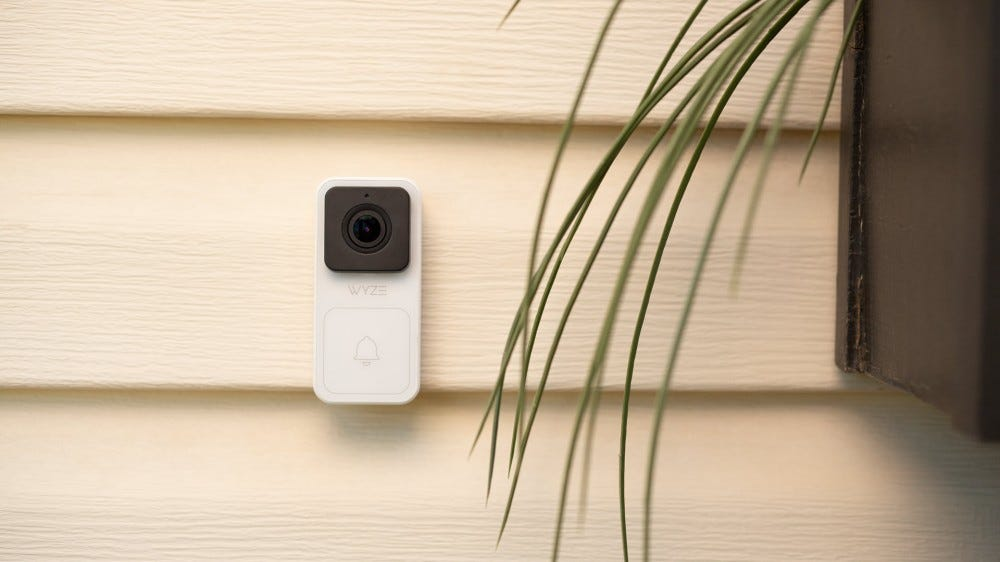 A Wyze video doorbell mounted on a white home.
