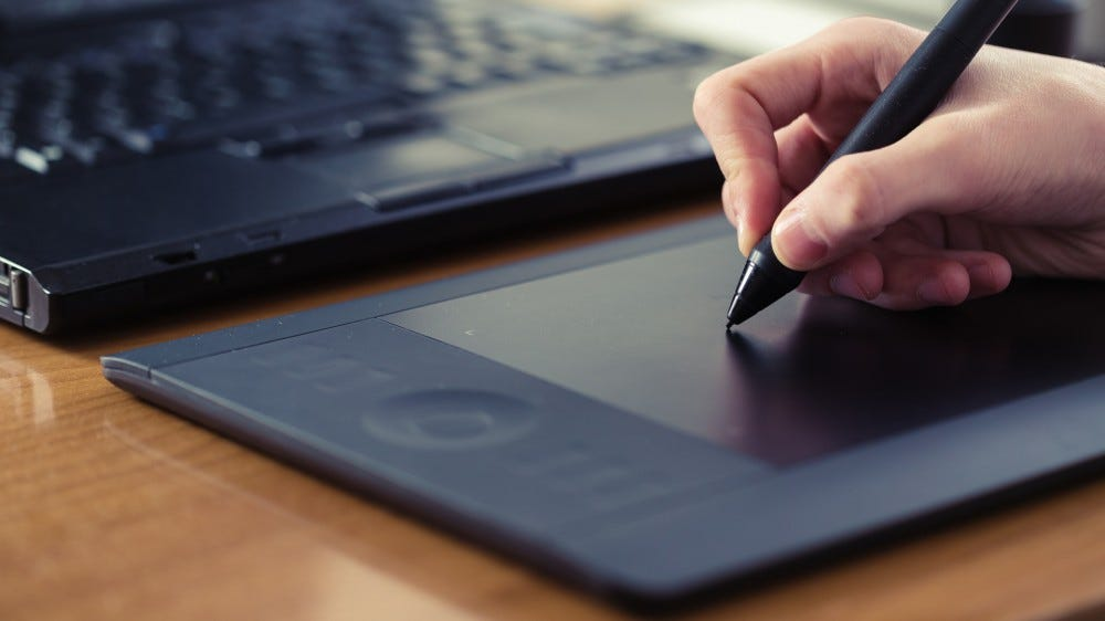 Person using graphics tablet on desk