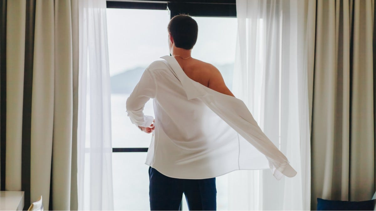 A man putting on a button-up shirt in front a window
