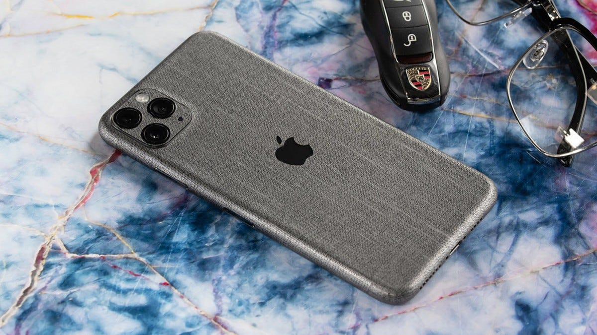 An iPhone covered in an grey SlickWraps skin.
