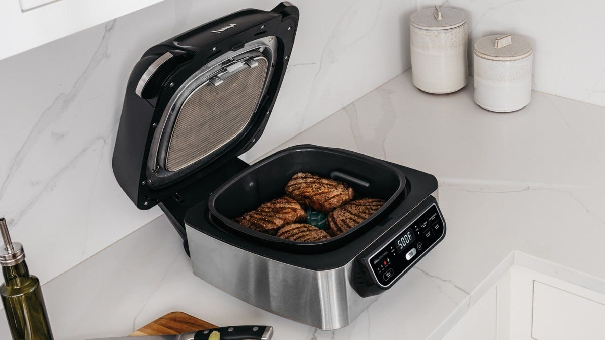Image of grill with steaks on the grill plate