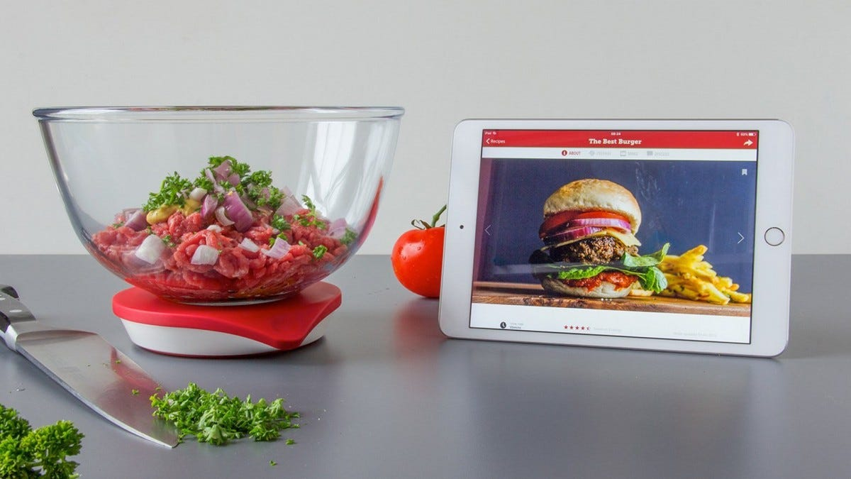 The Drop smart scale in use. It has no display, and it's the size of a small tupperware container.