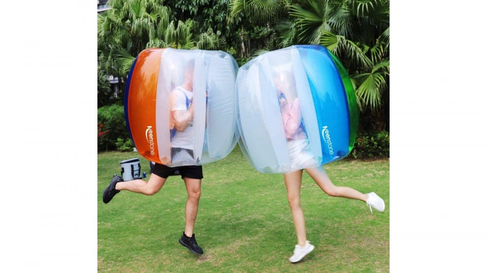 Friends in inflatable bumper ball suits running into each other in a backyard