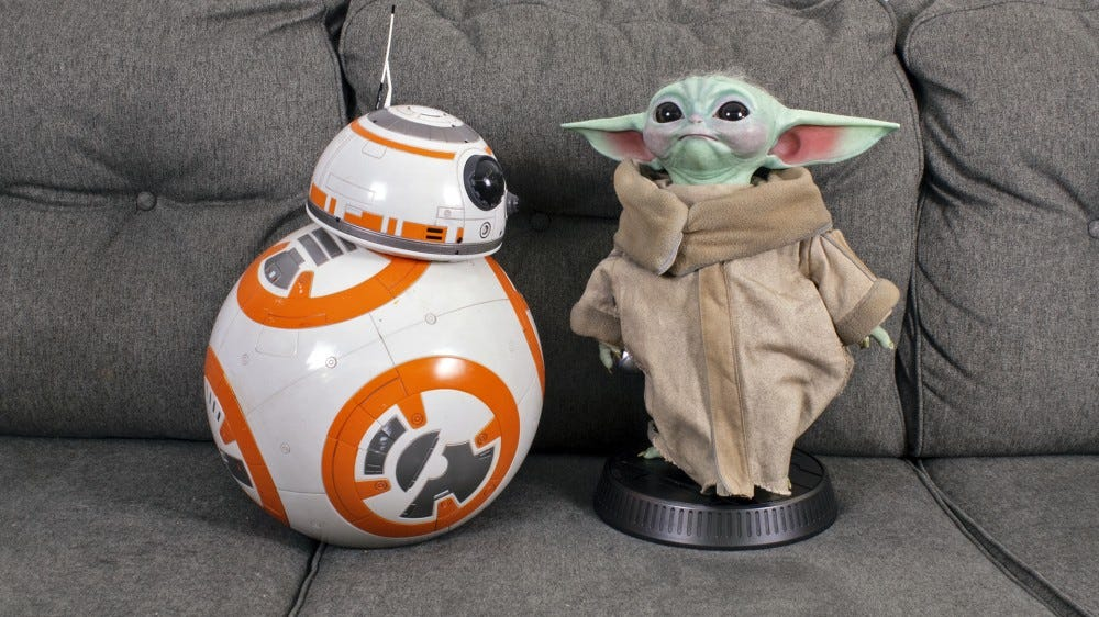 Baby Yoda next to a large replica of BB-8