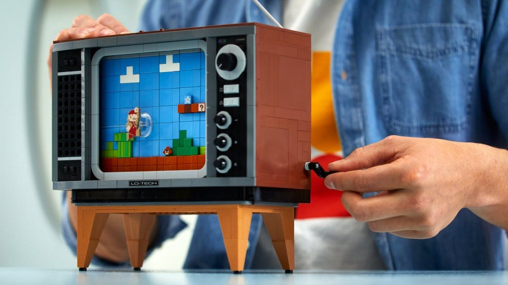 A closeup of the LEGO TV, while someone handcranks the screen.