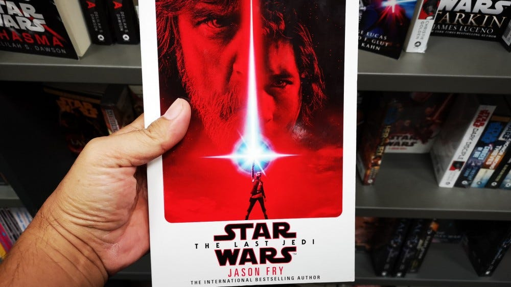 "Hand holding ""Star Wars: The Last Jedi"" book by author Jason Fry in a bookstore"
