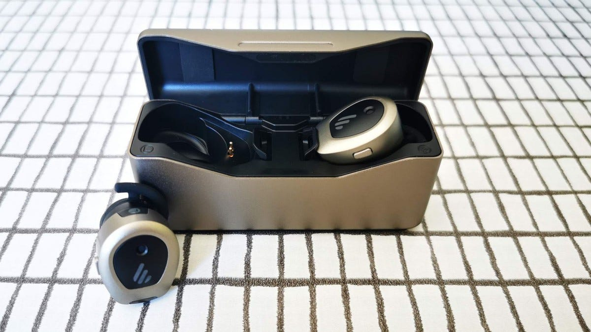 TWS NB headphones one in open case one on table