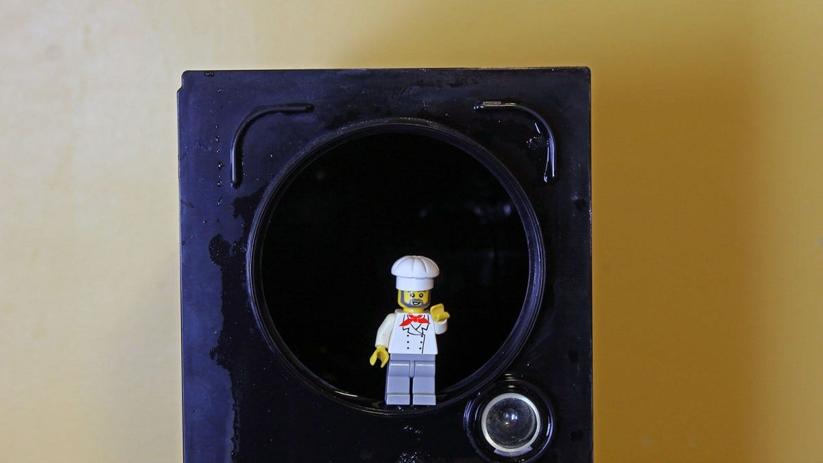 The bottom of a tank with a LEGO mini fig standing in a hole, his head just reaching the center.