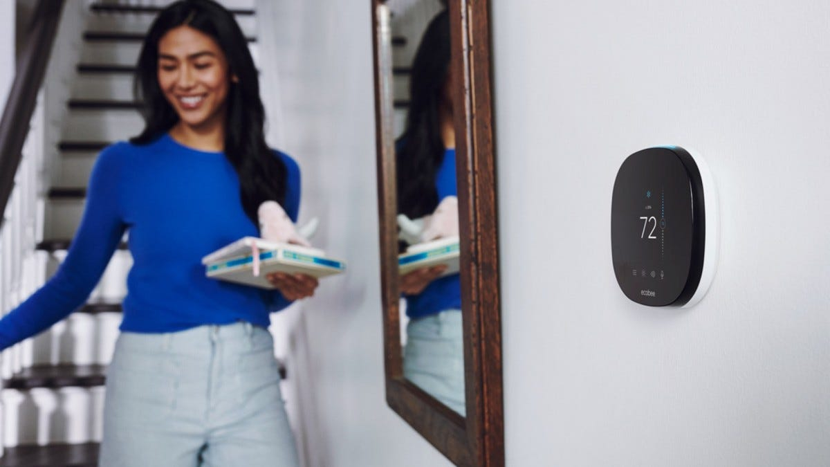 A photo of a woman walking by her ecobee SmarThermostat.