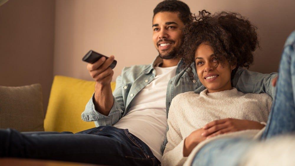 A young couple enjoying free TV.