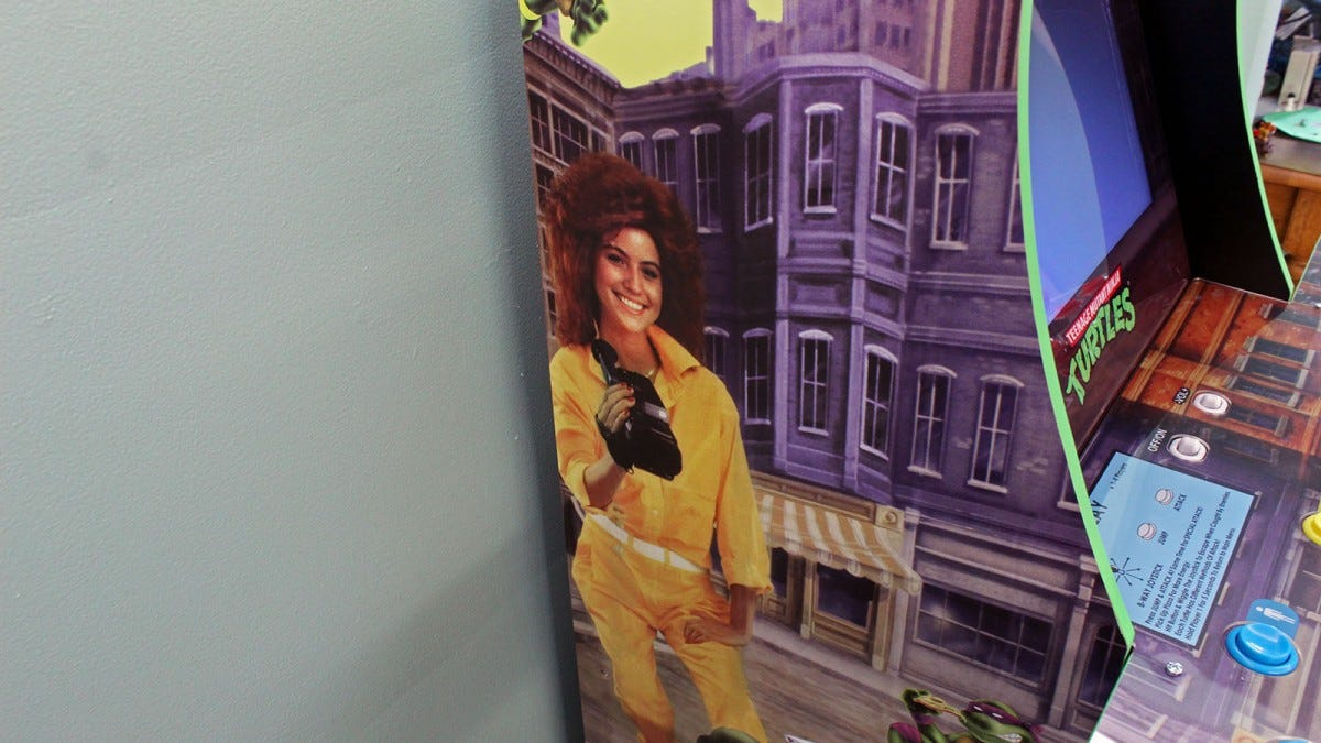 "A woman in a yellow jumpsuit with teased red hair holding an old camcorder on the side of the Arcade1Up ""Teenage Mutant Ninja Turtles"" arcade."