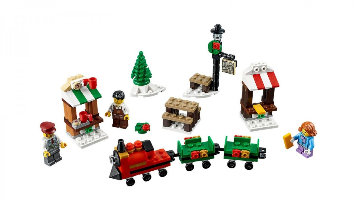 A LEGO train set, with lamppost, shops, and tree.