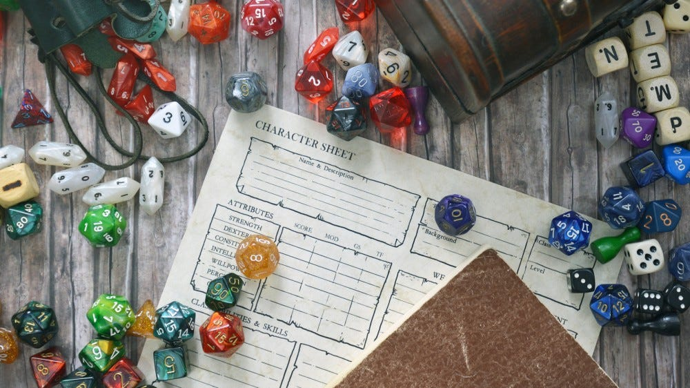 Tabletop role playing flat lay with colorful RPG game dice, character sheet, rule book, and treasure chest on wooden table