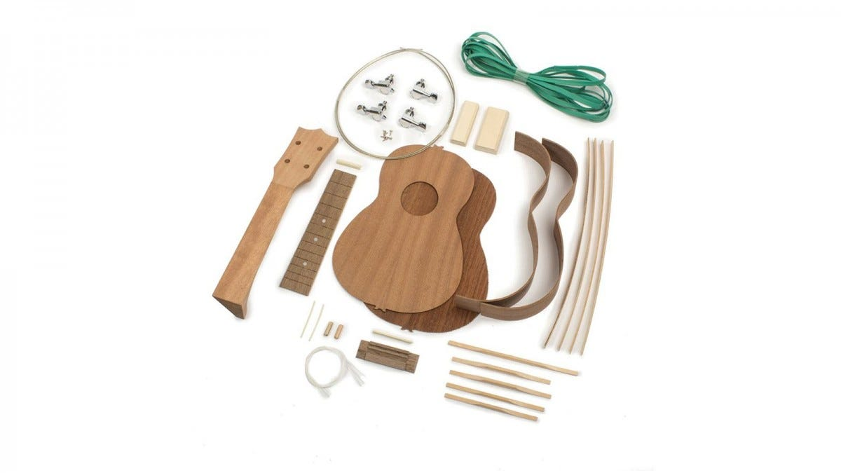 A disassembled Ukulele, with strings, green rubber bands, and tuner pieces.