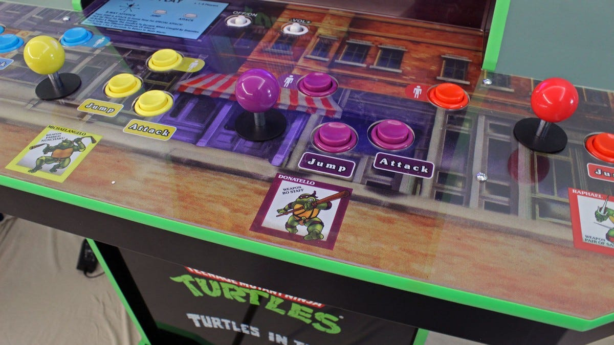 "The controller, buttons, and Michelangelo in a yellow mask and bands on the ""Teenage Mutant Ninja Turtles"" arcade."
