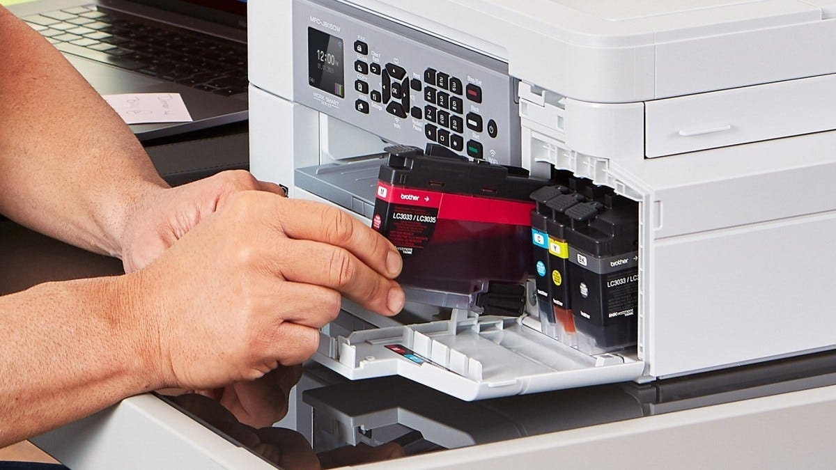 Man's hands inserting a printer cartridge into a printer.