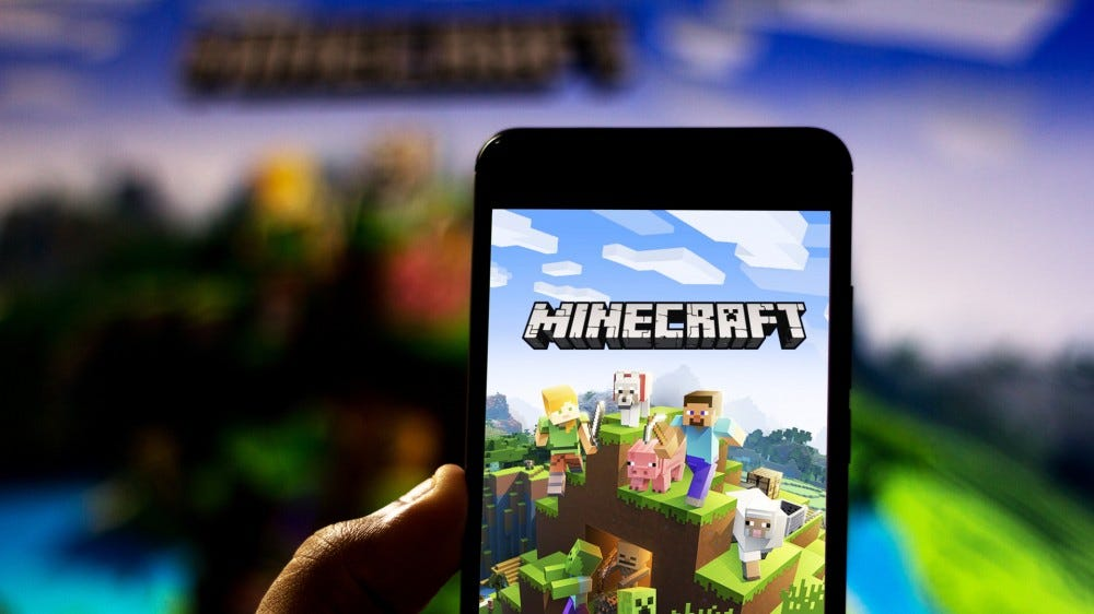 Minecraft logo on Android mobile device, held in front of TV with the game loaded