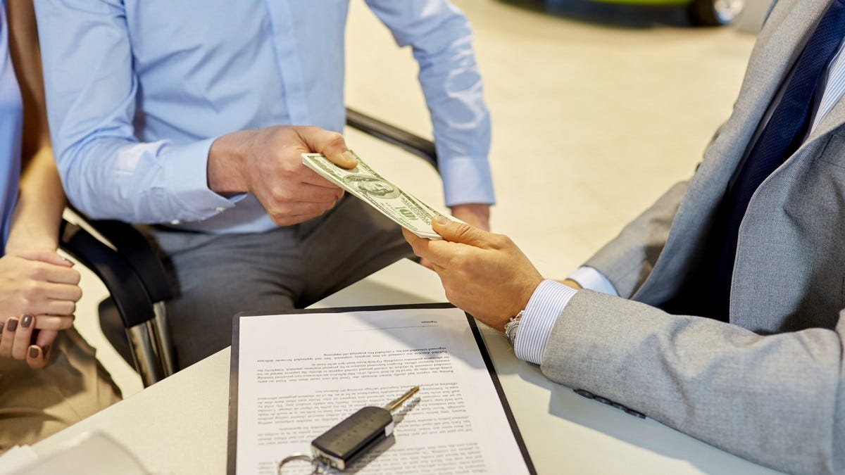 A man's hand handing a stack of money to another man's hand over a table with a contract and a car key sitting on it.