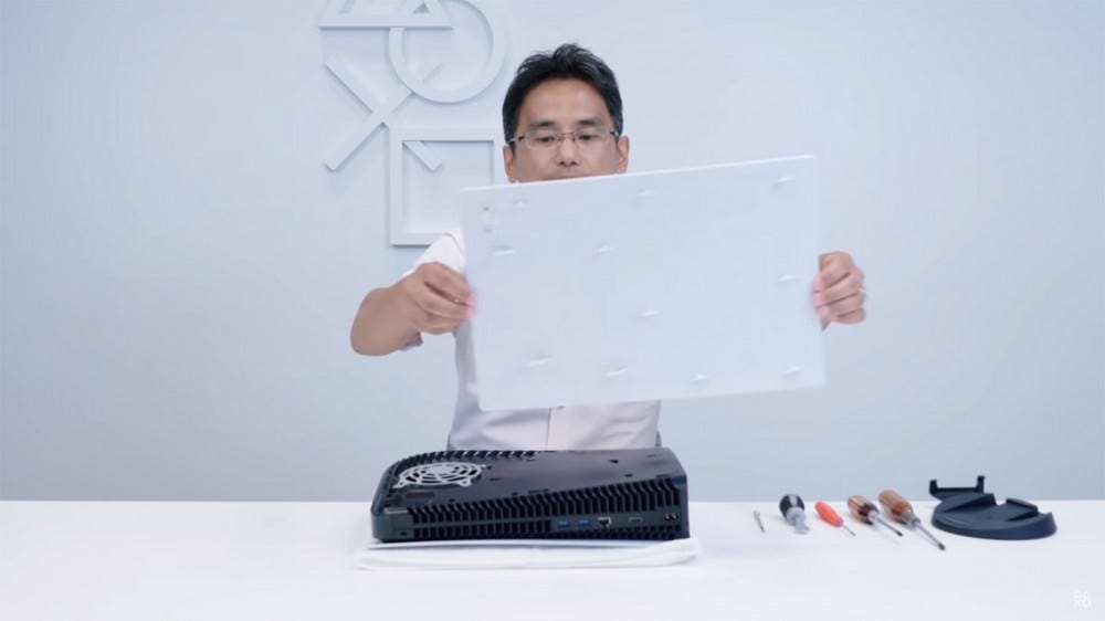 PS5 teardown video screenshot: engineer holds plastic cover above console.
