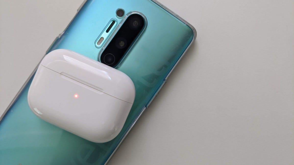 A pair of true wireless earbuds in a case, sitting atop a OnePlus 8 Pro phone.