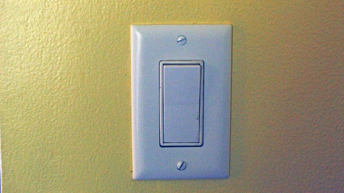 A standard light switch in the off position.