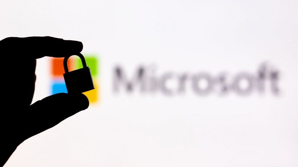 A shadow profile of a padlock held over the Microsoft logo