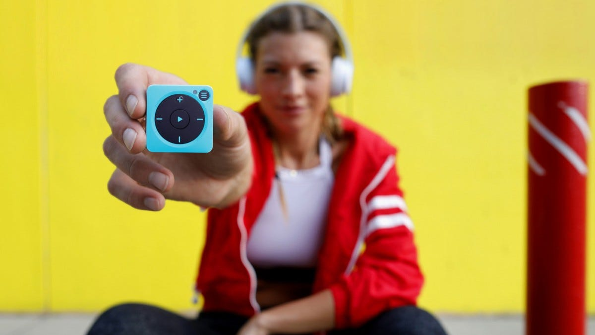 A woman wearing headphones and holding out a Mighty Vibe music player.