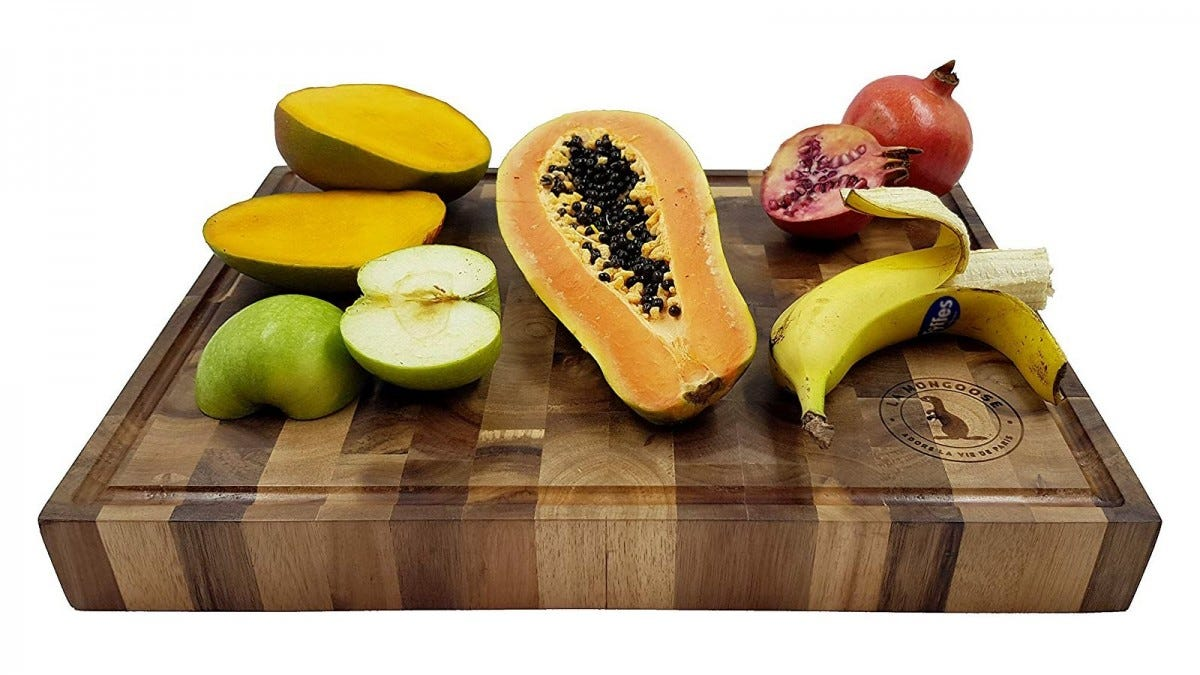 A large cutting board with a banana, apple, and other fruit on it.