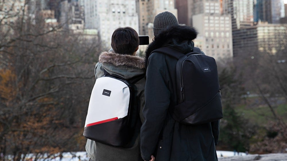 Two people wearing Urban Traveler backpacks.