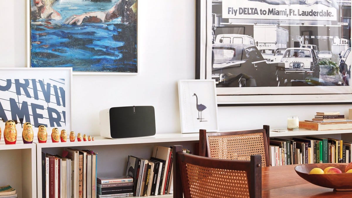 A Sonos Play 5 on a bookshelf next to paintings.