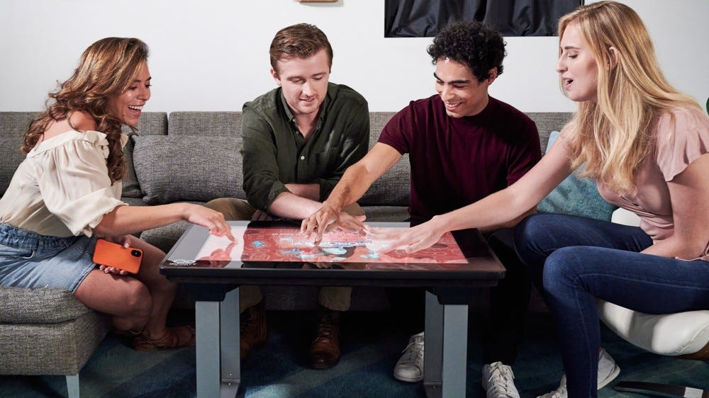 Four people playing on an electronic board game table.