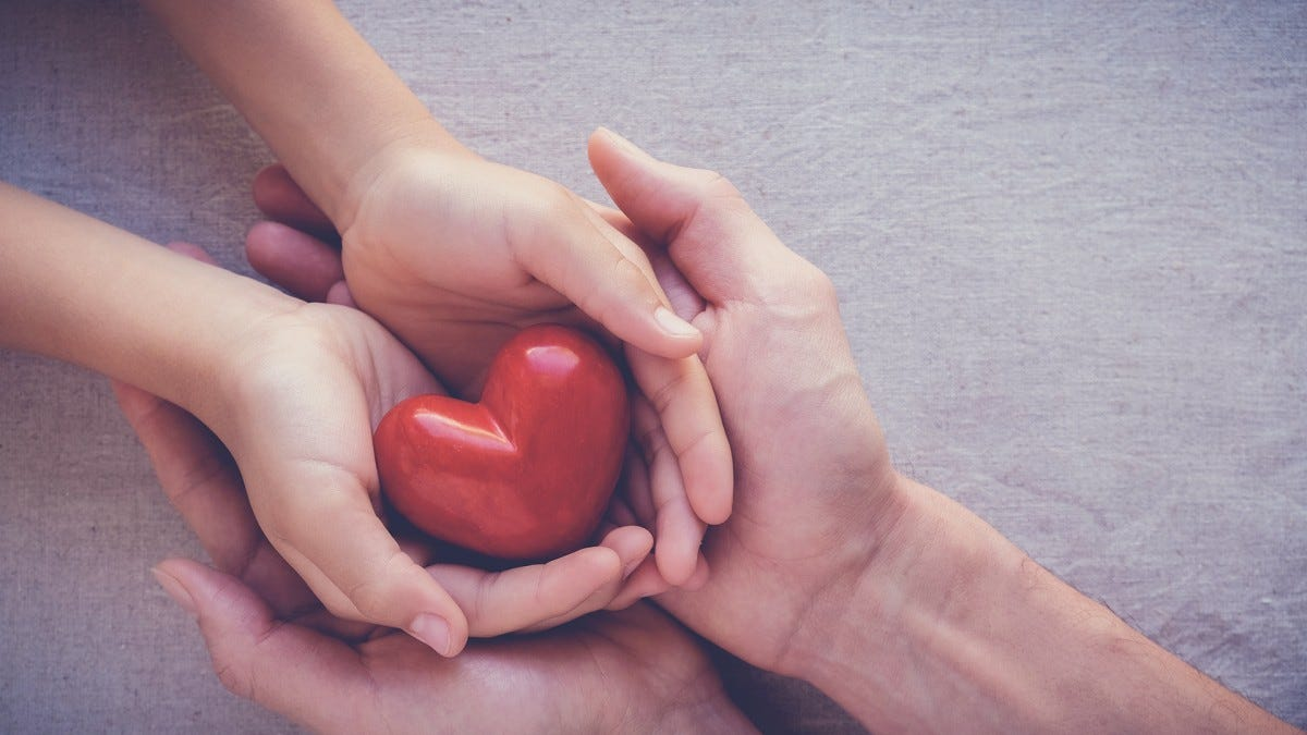 A child and an adult have a heart in their hands.