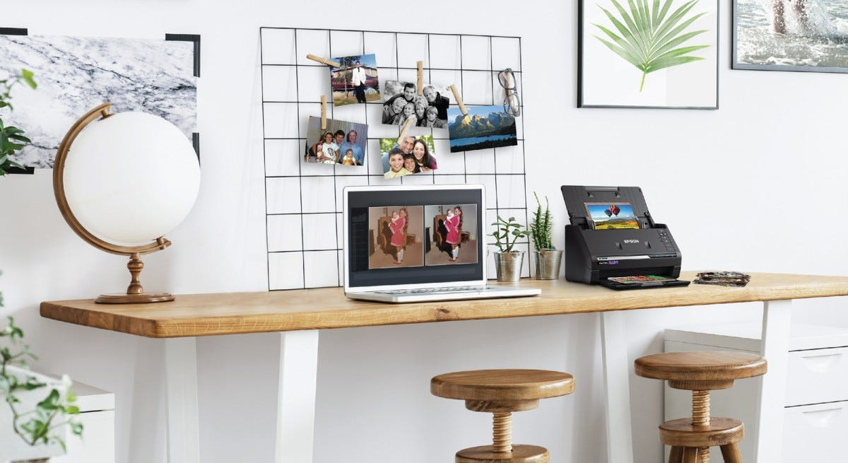 The Epson FastFoto FF-680W on a desk printing images from a laptop sitting next to it.